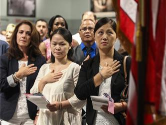 A group of adult with their hands on their chest taking a pledge
